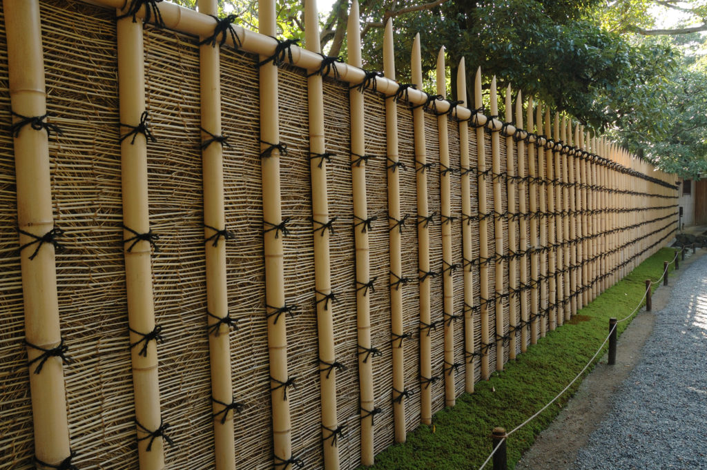 A bamboo fence is used in a yard to line a stone-covered path.