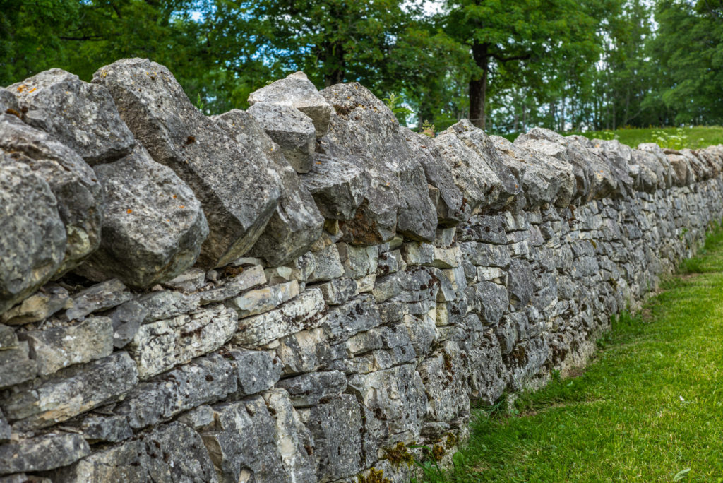 A gorgeous stone wall enclosing a lawn for a home or business.