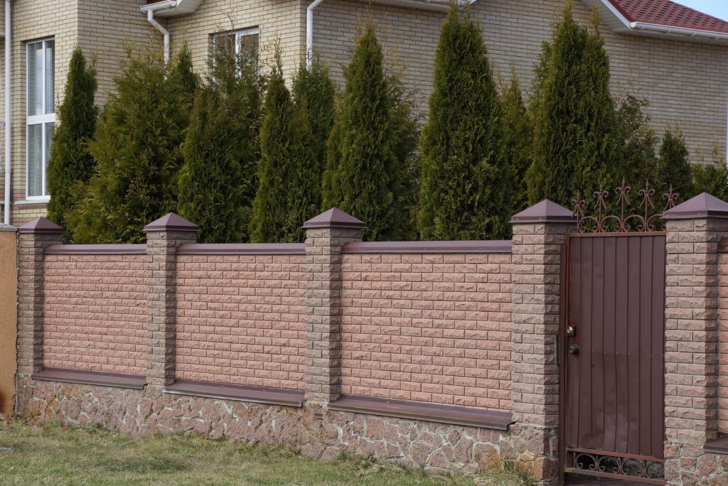 A brick wall with an ornate gate that's enclosing a front yard.