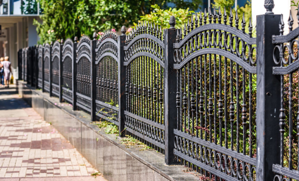 A decorative wrought iron fence enclosing a yard.