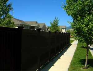 A black vinyl fence enclosing a yard along a sunlit sidewalk, showing the importance of cleaning your vinyl fence regularly.