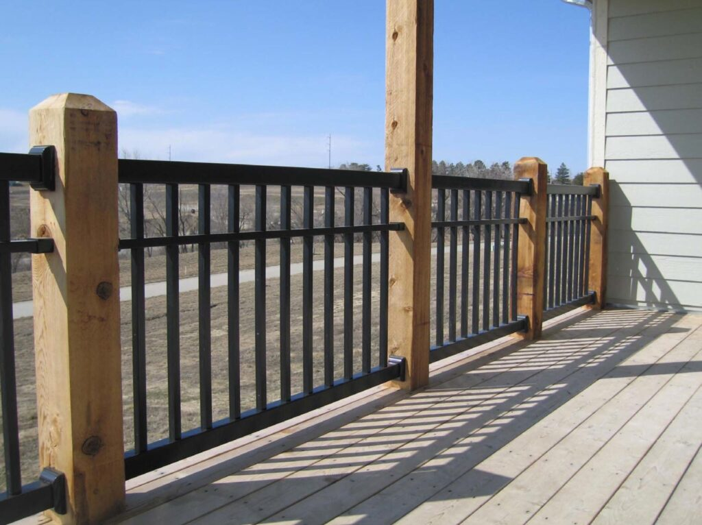 A black vinyl porch railing with wooden posts looking out over a dirt field.