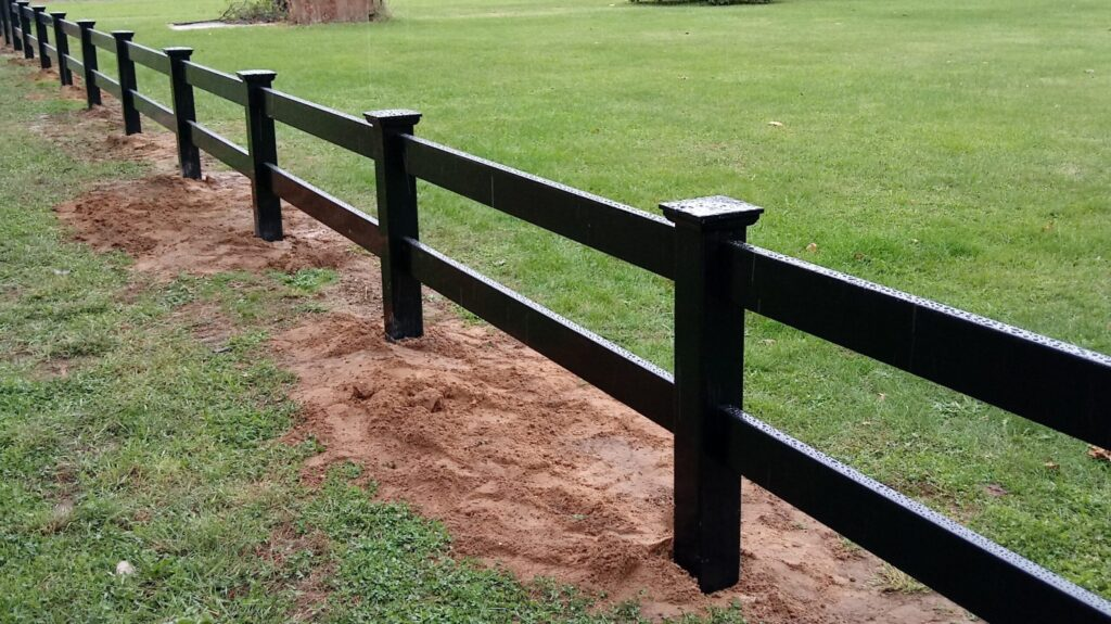 A black vinyl 2-rail ranch fence, made by Blackline HHP, surrounded on either side by green grass.