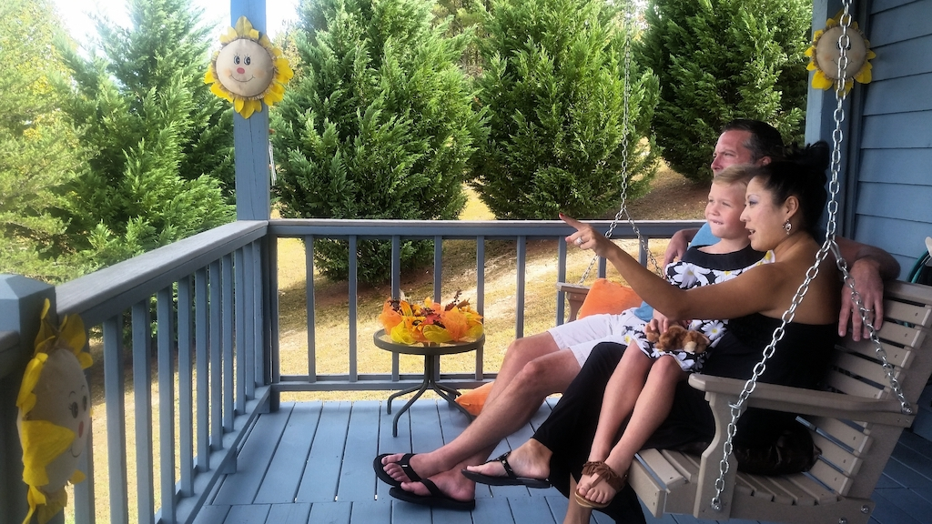 A family enjoys their new deck by looking at the beautiful scenery.