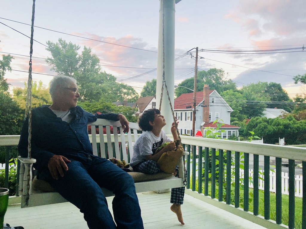 Grandpa and grandson sit on a porch swing on a patio with top-notch deck railing materials.